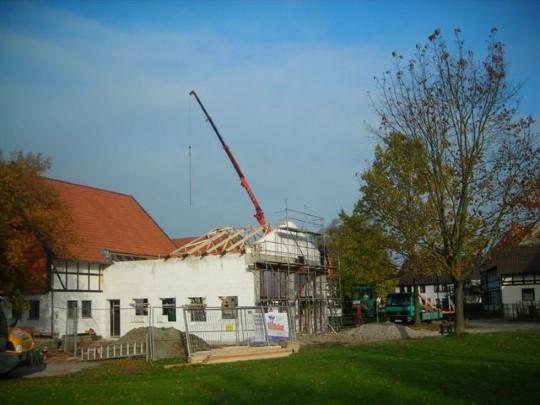 Mit einem Autokran wird der Dachstuhl auf die Erweiterung des Feuerwehrgerätehauses 'gehievt'...